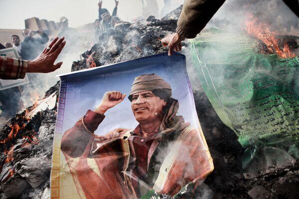 Жители Бенгази сжигают портреты Муамара Каддафи, плакаты с его цитатами и Зеленую книгу Каддафи - Sputnik Mundo