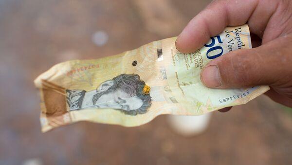 Una pepita de oro en un billete de bolívaro - Sputnik Mundo