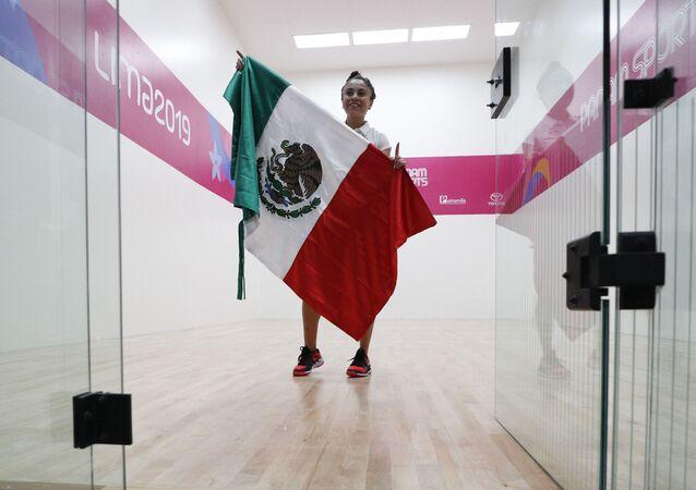 Paola Longoria sostiene la bandera de México tras derrotar a la argentina María Vargas