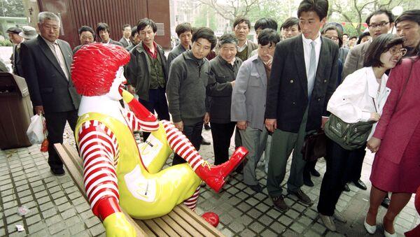 Unos chinos pasan al lado de una estatua de McDonalds - Sputnik Mundo