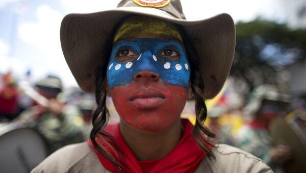 Una mujer con el rostro pintado con los colores de la bandera de Venezuela - Sputnik Mundo