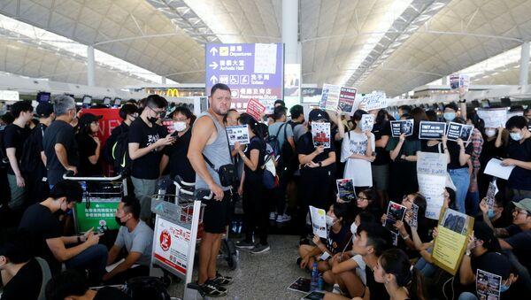 Un pasajero, esperando la embarcación durante las protestas en Hong Kong - Sputnik Mundo
