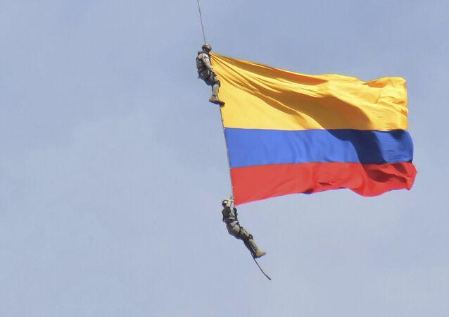 Dos soldados con la bandera de Colombia, colgados de un helicóptero, durante un espectáculo aéreo