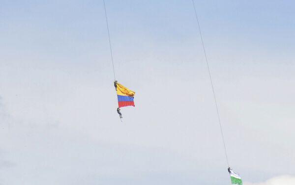 Dos soldados con la bandera de Colombia, colgados de un helicóptero, durante un espectáculo aéreo - Sputnik Mundo
