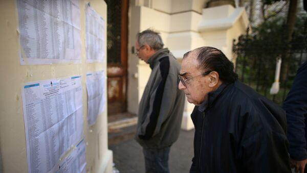 Un hombre observa las listas de votantes durante las elecciones primarias en Argentina - Sputnik Mundo