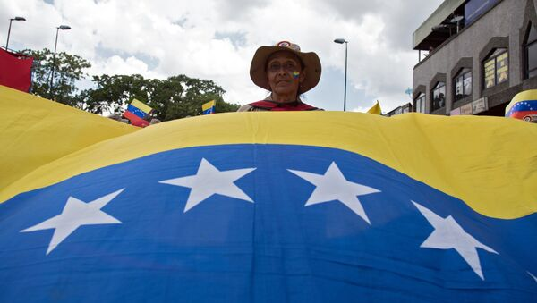 Una participante de una marcha en Caracas contra la política de sanciones de Estados Unidos - Sputnik Mundo