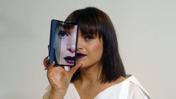 Una joven con un smartphone en la mano - Sputnik Mundo