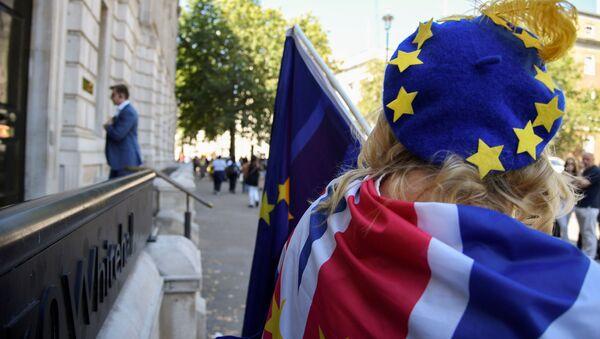 Una mujer con la bandera del Reino Unido y una boina con las estrellas de la UE - Sputnik Mundo