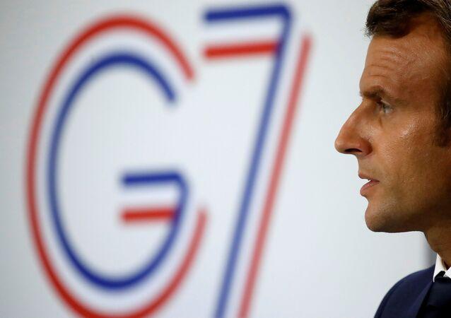 El presidente de Francia, Emmanuel Macron, y el logo de la cumbre del G7 en Biarritz