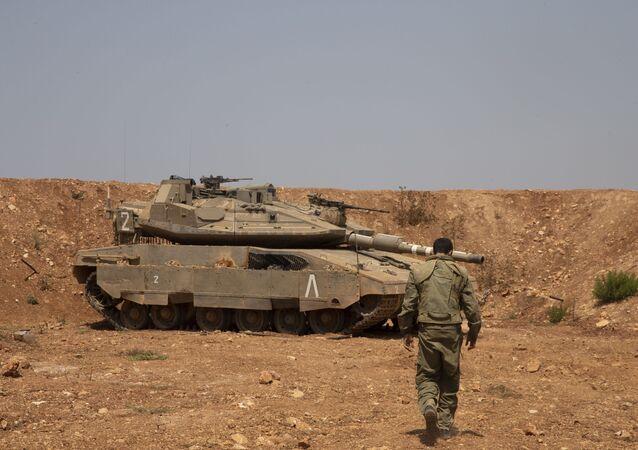 Un soldado israelí camina hacia el tanque en la frontera con Líbano