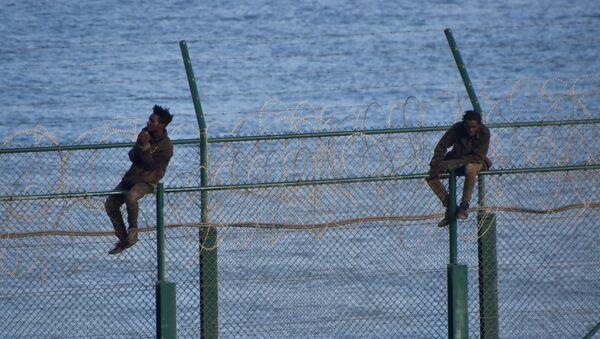 Migrantes en la valla fronteriza que separa la ciudad autónoma española de Ceuta de Marruecos - Sputnik Mundo