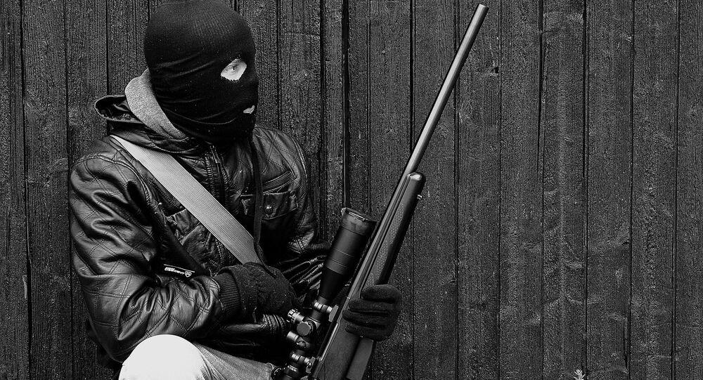Un hombre en un pasamontañas con un arma