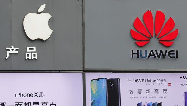 Los logotipos de Apple y Huawei se exhiben fuera de una tienda de telefonía móvil en Shenzhen, China - Sputnik Mundo