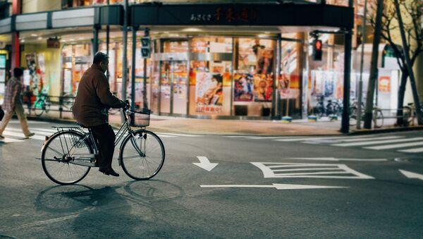 Hombre andando en bicicleta en Tokio - Sputnik Mundo