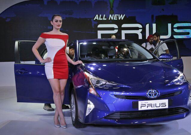 Una modelo posa junto al coche híbrido Prius de cuarta generación de Toyota