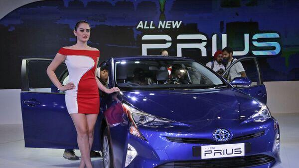 Una modelo posa junto al coche híbrido Prius de cuarta generación de Toyota  - Sputnik Mundo