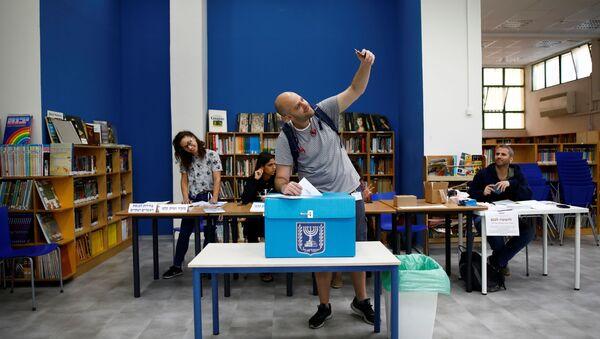 Un hombre votando en Tel Aviv, Israel - Sputnik Mundo