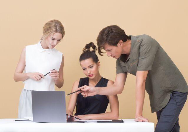 Varias personas trabajan con un laptop