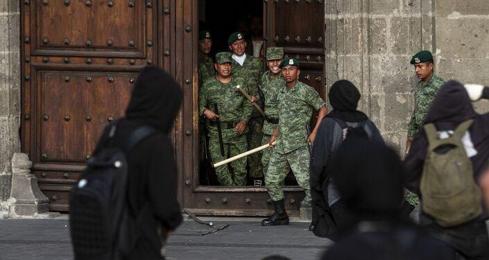 Manifestantes grafitean la puerta del Palacio Nacional, sede de la Presidencia de los Estados Unidos mexicanos durante la marcha a cinco años de la desaparición forzada de los estudiantes.