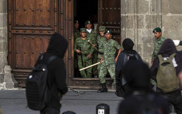 Manifestantes grafitean la puerta del Palacio Nacional, sede de la Presidencia de los Estados Unidos mexicanos durante la marcha a cinco años de la desaparición forzada de los estudiantes.  - Sputnik Mundo