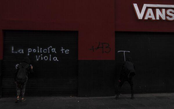 Asistentes a la manifestación a cinco años de la desaparición forzada de los 43 estudiantes de Ayotzinapa grafitean a su paso. - Sputnik Mundo
