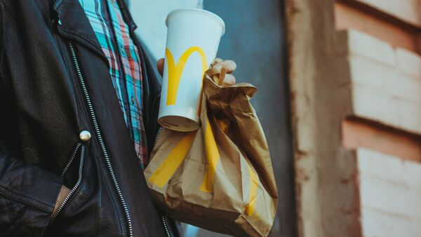 Una persona con alimentos de McDonald's - Sputnik Mundo