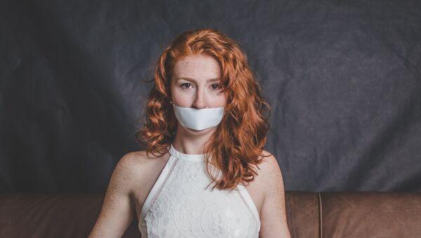 Una joven con una cinta en la boca - Sputnik Mundo