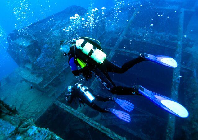 Dos buzos inspeccionan los restos de un barco naufragado