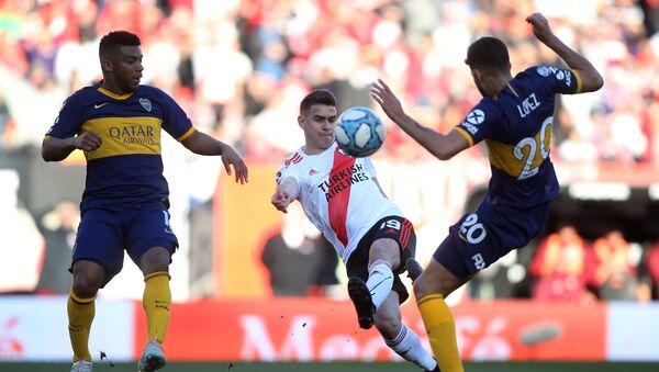 El futbolista de River Plate Rafael Santos Borré disputa el balón con Lisandro López de Boca Juniors - Sputnik Mundo