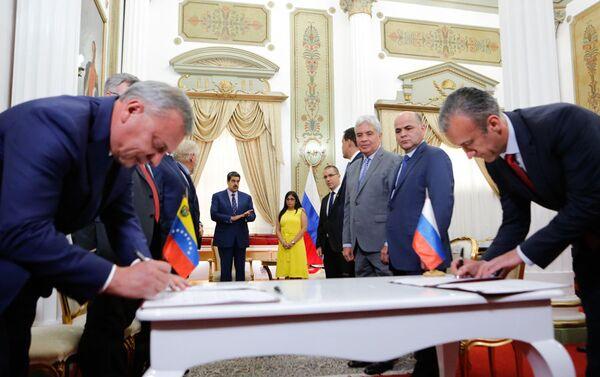 El vice primer ministro de Rusia, Yuri Borísov, firmando varios acuerdos junto al vicepresidente del Área Económica y ministro de Industrias y Producción Nacional de Venezuela, Tareck El Aissami - Sputnik Mundo