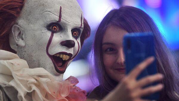 Una visitante de Comic Con se hace un selfí con un 'cosplayer' del payaso Pennywise - Sputnik Mundo