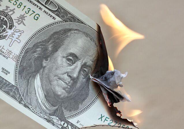 Un billete de dólares estadounidenses en llamas