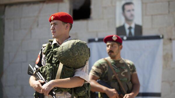 Un soldado ruso y otro sirio ante el retrato del presidente Bashar Asad - Sputnik Mundo