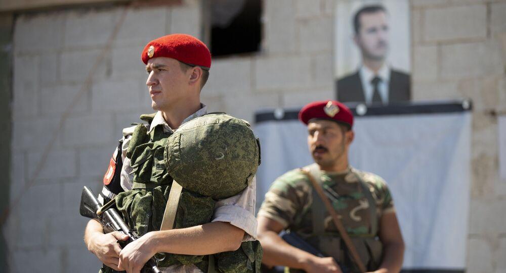 Un soldado ruso y otro sirio ante el retrato del presidente Bashar Asad (archivo)