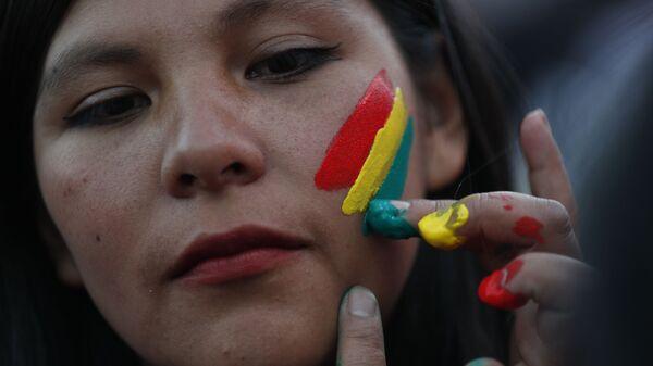 Una mujer pinta los colores de la bandera boliviana en su rostro - Sputnik Mundo
