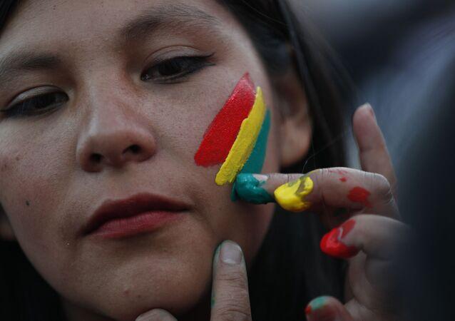 Una mujer pinta los colores de la bandera boliviana en su rostro