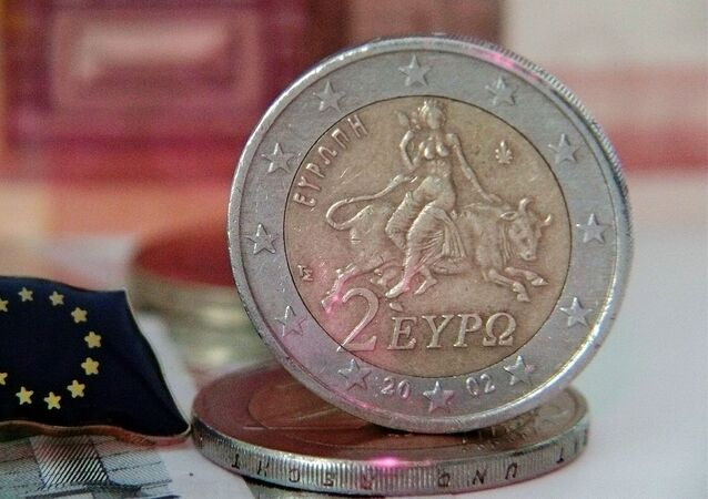 Una moneda de euro y la bandera de la UE