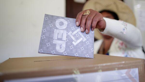 Una persona deposita su voto en las urnas en las elecciones generales en Bolivia - Sputnik Mundo