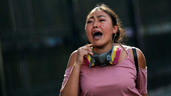 Una mujer chilena corre durante las protestas en Santiago - Sputnik Mundo