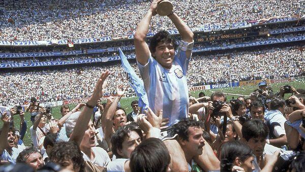 Diego Maradona sosteniendo la Copa del Mundo en 1986, en el Estadio Azteca. - Sputnik Mundo