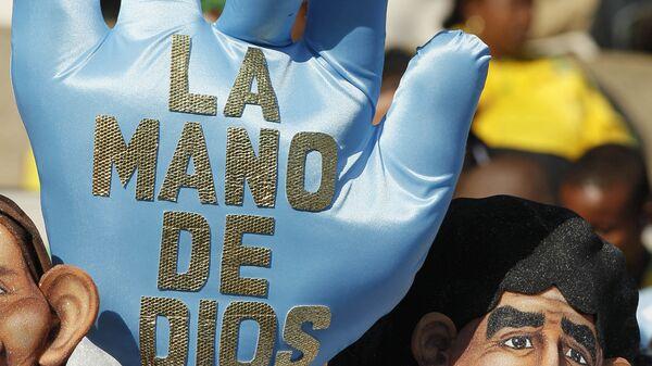 Аргентинский болельщик в маске, изображающей Марадону, и с перчаткой, на которой написано: Рука бога перед матчем Аргентина - Нигерия группового этапа ЧМ 2010 - Sputnik Mundo