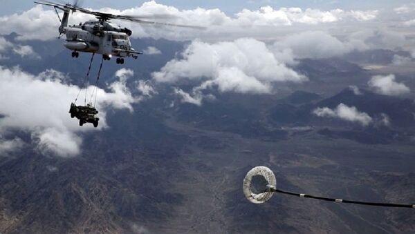 Un helicóptero realiza un repostaje aéreo mientras carga un todoterreno - Sputnik Mundo