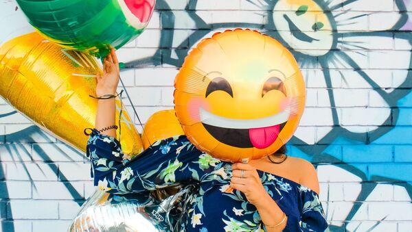 Una persona sostiene un balón de emoji sobre su rostro - Sputnik Mundo