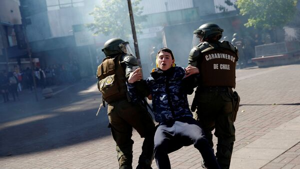 Carabineros de Chile atrapan a un manifestante durante una protesta - Sputnik Mundo