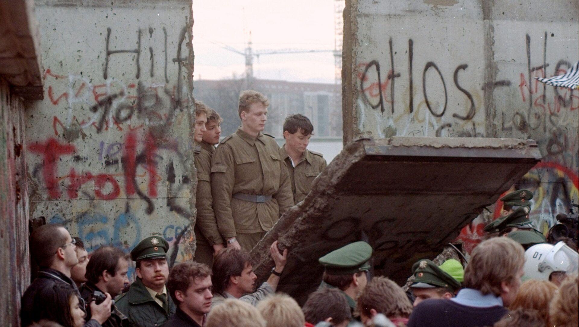 Guardias fronterizos de Alemania Oriental aparecen tras el muro de Berlín después que los manifestantes derribaron un segmento  - Sputnik Mundo, 1920, 08.11.2019