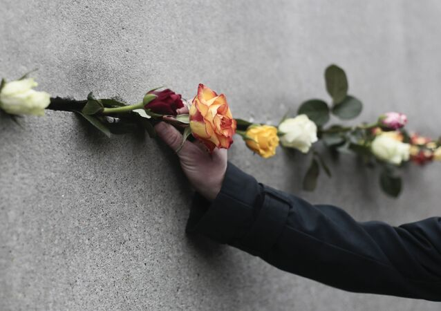 Un hombre coloca una flor en una grieta del Muro de Berlín