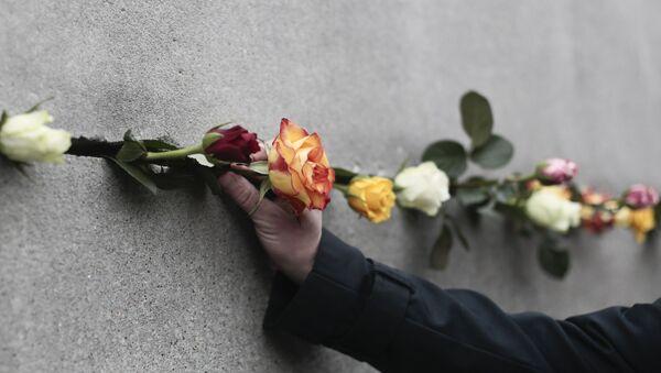 Un hombre coloca una flor en una grieta del Muro de Berlín - Sputnik Mundo