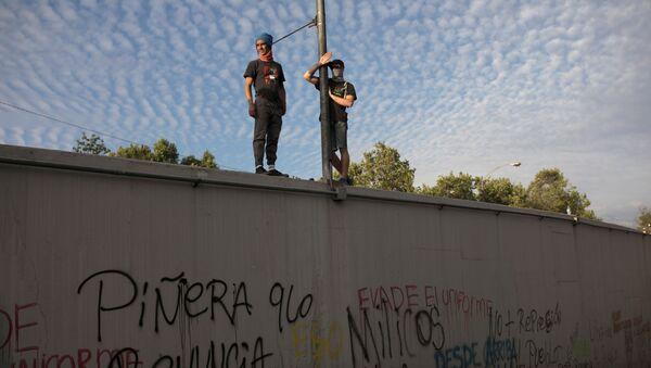 Manifestantes chilenos contra el Gobierno de Chile parados sobre un muro en Santiago - Sputnik Mundo