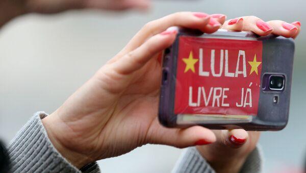 Una mujer sostiene un teléfono celular con un mensaje en apoyo a Lula - Sputnik Mundo