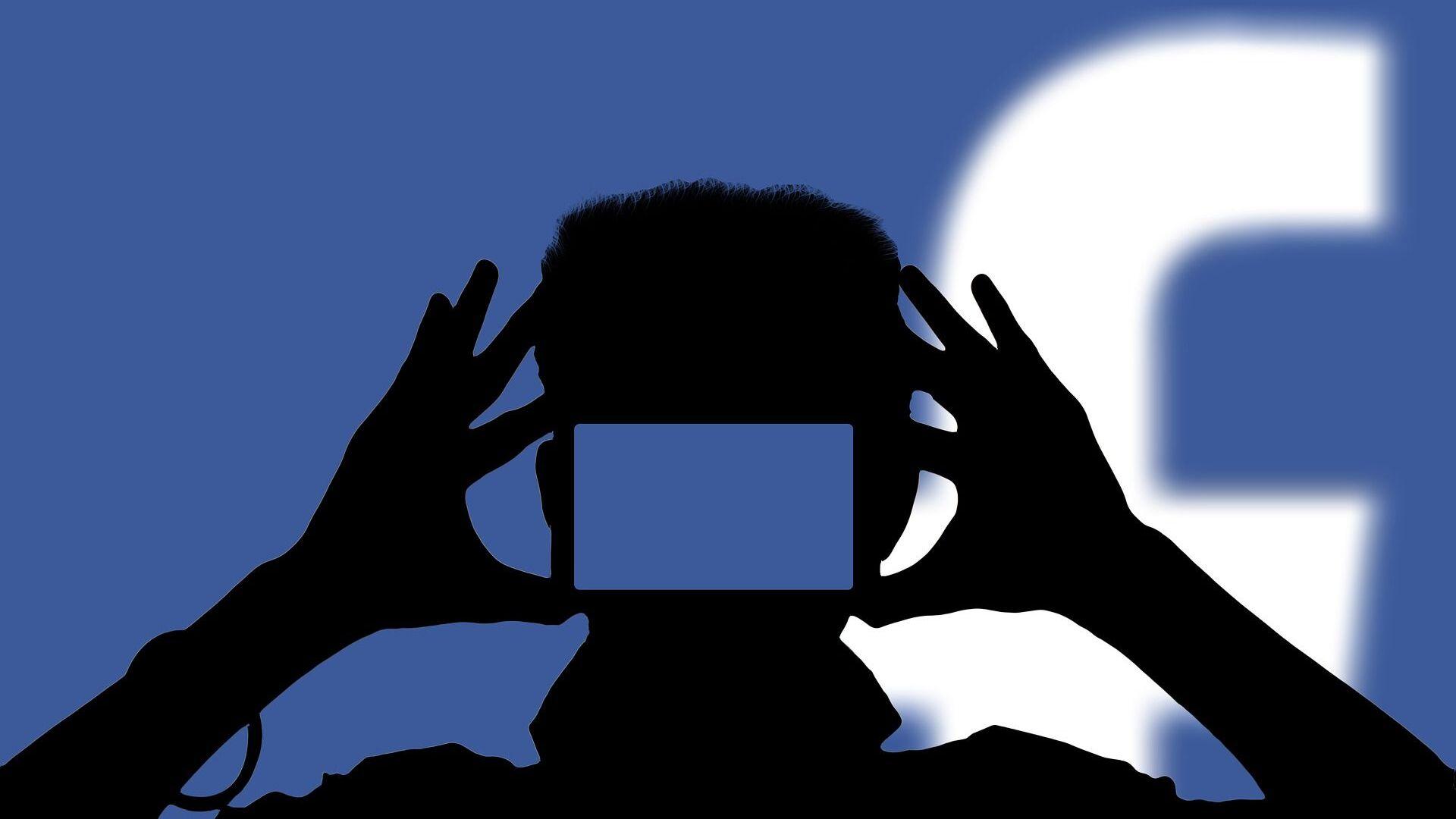Una persona con un teléfono móvil con el logo de Facebook de fondo - Sputnik Mundo, 1920, 18.02.2021